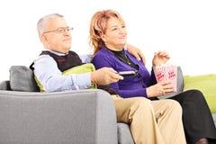 Pares maduros que ven la TV y que comen las palomitas asentadas en un sofá Imagenes de archivo