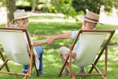 Pares maduros relaxado que sentam-se em cadeiras de plataforma no parque foto de stock