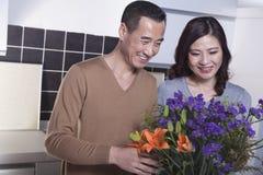 Pares maduros sonrientes que miran un ramo colorido de flores en la cocina Imagenes de archivo
