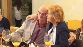 Pares mais velhos bonitos que abraçam no restaurante filme