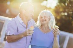Pares mais velhos que comem o gelado e o passeio imagem de stock royalty free