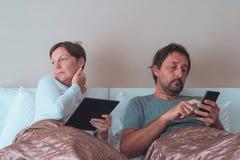 Pares, marido y esposa aburridos en dormitorio fotos de archivo libres de regalías