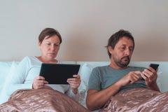 Pares, marido y esposa aburridos en dormitorio fotografía de archivo