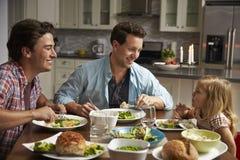 Pares masculinos e filha alegres que jantam em sua cozinha Foto de Stock