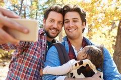 Pares masculinos gay con el bebé que toma Selfie en paseo en arbolado Imágenes de archivo libres de regalías