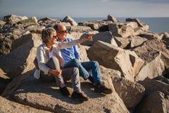Pares mayores activos que caminan en rocas soleadas por el mar imagenes de archivo