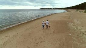 Pares mayores activos que caminan a través de la playa junto metrajes
