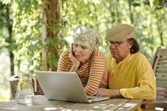 Pares mayores al aire libre con un ordenador portátil Imagenes de archivo