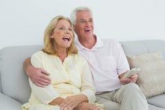 Pares mayores alegres con teledirigido en casa Foto de archivo