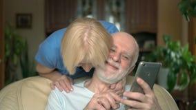 Pares mayores alegres en casa Marido que usa smartphone, hojeando, leyendo Abrazo que viene de la esposa almacen de video