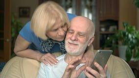 Pares mayores alegres en casa Marido que usa smartphone, hojeando, leyendo Abrazo que viene de la esposa almacen de metraje de vídeo