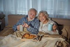 Pares mayores alegres que tienen comida en dormitorio fotos de archivo