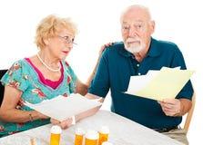 Pares mayores apenados por las cuentas médicas Foto de archivo libre de regalías