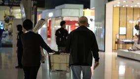Pares mayores asiáticos felices en viaje con franquicia de la familia de la diversión del aeropuerto almacen de video