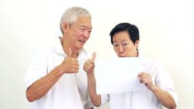 Pares mayores asiáticos felices video que llevan a cabo la muestra en blanco blanca lista para la bandera de la publicidad de la  almacen de video