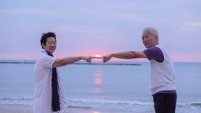 Pares mayores asiáticos junto en la playa de la salida del sol Año Nuevo, nuevo cha Imagen de archivo libre de regalías