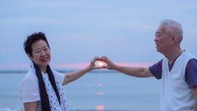 Pares mayores asiáticos junto en la playa de la salida del sol Año Nuevo, nuevo cha Fotos de archivo libres de regalías