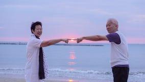 Pares mayores asiáticos junto en la playa de la salida del sol Año Nuevo, nuevo cha Fotos de archivo