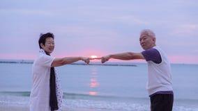 Pares mayores asiáticos junto en la playa de la salida del sol Año Nuevo, nuevo cha Fotografía de archivo