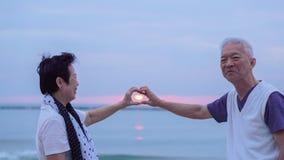 Pares mayores asiáticos junto en la playa de la salida del sol Año Nuevo, nuevo cha Imagenes de archivo