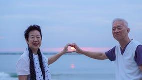 Pares mayores asiáticos junto en la playa de la salida del sol Año Nuevo, nuevo cha Foto de archivo