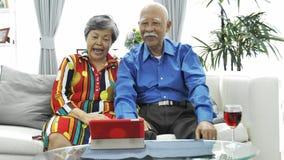 Pares mayores asiáticos que tienen charla video de la diversión en móvil de la tableta almacen de video