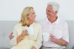 Pares mayores cariñosos con las tazas de café en casa Imagen de archivo