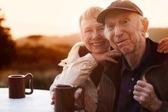 Pares mayores cariñosos en la puesta del sol fotos de archivo libres de regalías