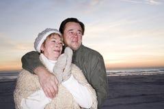 Pares mayores cariñosos en suéteres en la playa Imagenes de archivo
