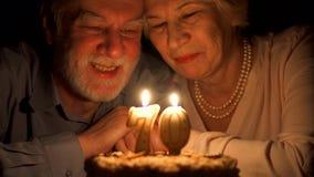 Pares mayores cariñosos que celebran aniversario con la torta en casa por la tarde Soplar hacia fuera velas