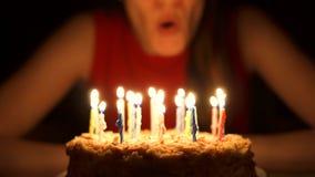 Pares mayores cariñosos que celebran aniversario con la torta en casa por la tarde Soplar hacia fuera velas almacen de video