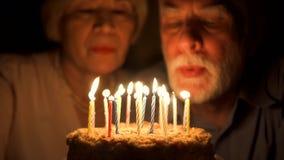 Pares mayores cariñosos que celebran aniversario con la torta en casa por la tarde Soplar hacia fuera velas metrajes