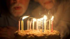 Pares mayores cariñosos que celebran aniversario con la torta en casa por la tarde Soplar hacia fuera velas almacen de metraje de vídeo