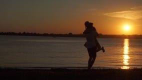 Pares mayores cariñosos que disfrutan de una tarde romántica de la puesta del sol que baila junto en la playa filmada almacen de video