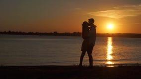 Pares mayores cariñosos que disfrutan de una tarde romántica de la puesta del sol que baila junto en la playa filmada metrajes