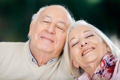 Pares mayores cariñosos que se relajan con los ojos cerrados Imagenes de archivo