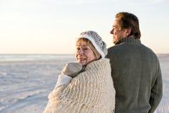 Pares mayores cariñosos en suéteres en la playa Foto de archivo