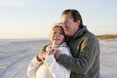 Pares mayores cariñosos en suéteres en la playa Foto de archivo libre de regalías