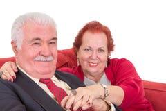 Pares mayores cariñosos en un sofá rojo Fotos de archivo