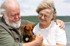 Pares mayores con el Dachshund miniatura Fotografía de archivo libre de regalías