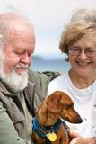 Pares mayores con el Dachshund miniatura Imagen de archivo libre de regalías