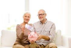 Pares mayores con el dinero y la hucha en casa Imagenes de archivo