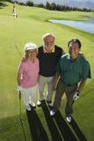 Pares mayores con el instructor en campo de golf Fotos de archivo libres de regalías