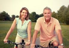 Pares mayores con la bicicleta Fotografía de archivo