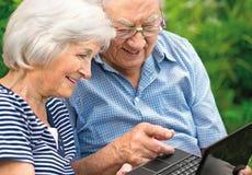 Pares mayores con la computadora portátil Foto de archivo libre de regalías