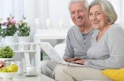 Pares mayores con la computadora portátil Imágenes de archivo libres de regalías