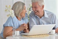 Pares mayores con la computadora portátil Fotografía de archivo