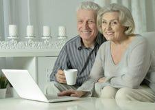 Pares mayores con la computadora portátil Foto de archivo