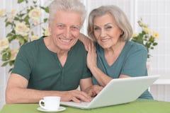 Pares mayores con la computadora portátil Imagenes de archivo