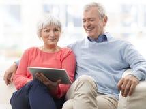 Pares mayores con la tableta de Digitaces Foto de archivo libre de regalías